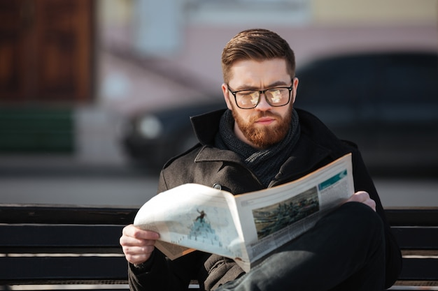 Concentrated young man sitting on bench and reading newspaper outdoors Free Photo