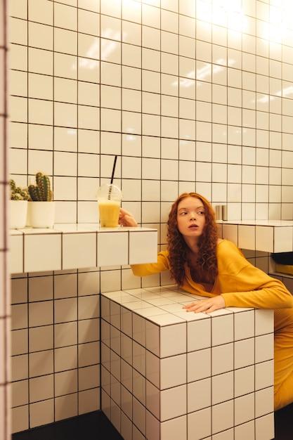 Signora riccia concentrata della giovane testarossa che si siede in caffè Foto Gratuite