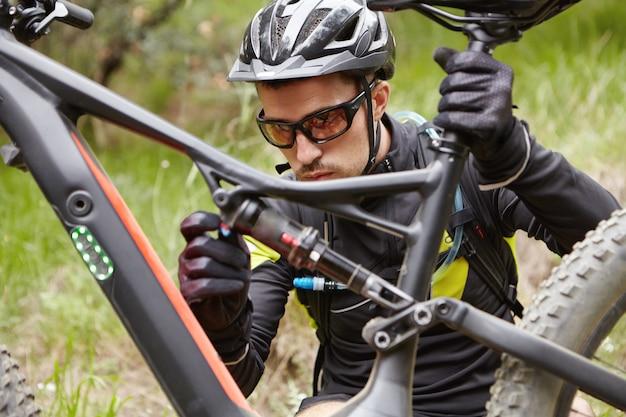 Concentrato giovane cavaliere in casco, occhiali e guanti seduto davanti alla sua bicicletta di richiamo Foto Gratuite