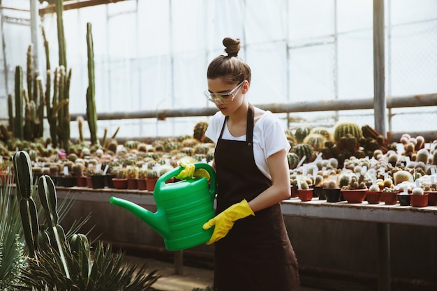 Concentrated young woman in glasses standing in greenhouse Free Photo