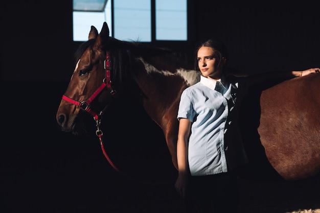 彼女の馬の近くに屋外で立っている若い女性を集中 無料写真