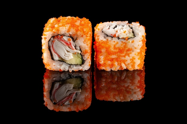 Concept of asian cuisine. two rolls of sushi with different fillings on a black background with the age for a japanese menu for a cafe, restaurant, sushi bar. Premium Photo
