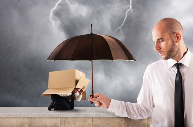 Concept of assistance in your business with a big businessman that holds an umbrella Premium Photo