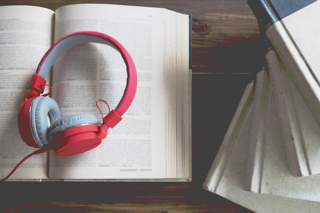 Concept of audiobook. books on the table with headphones put on them. Free Photo