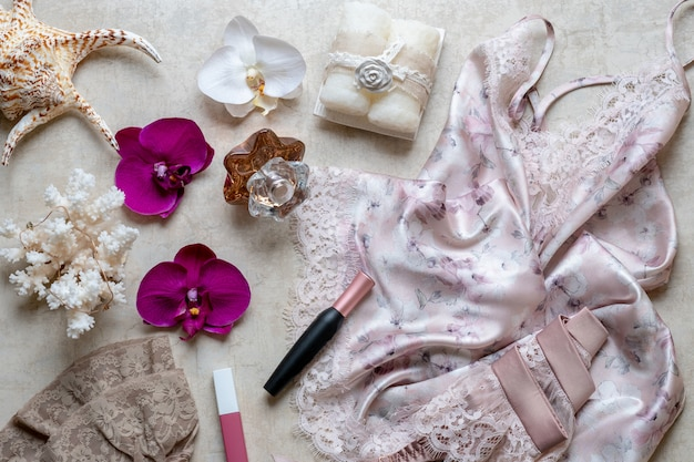 The concept of beauty in the blog, nightie, belt for stockings, cosmetics, perfume. Premium Photo