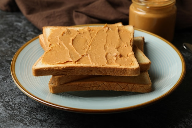 Concept of breakfast with peanut butter toast on black smokey table Premium Photo