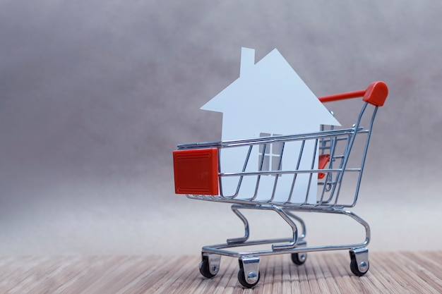 The concept of buying and selling a home. house with paper in the trolley. Premium Photo