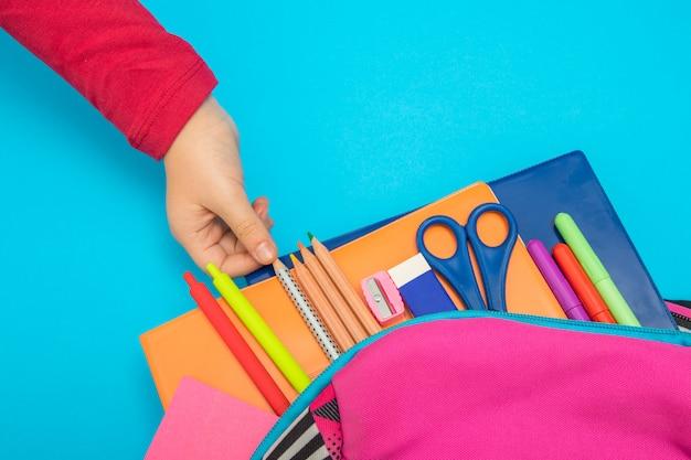 学校concept.child手に戻る色付きの背景にバックパックから学用品 Premium写真