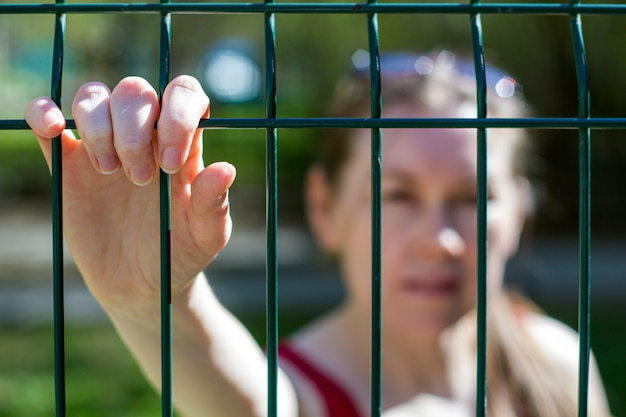 Concept of closure of the border, isolation. inability to leave. female hands on the lattice as a symbol of limitation, borders, waiting Premium Photo