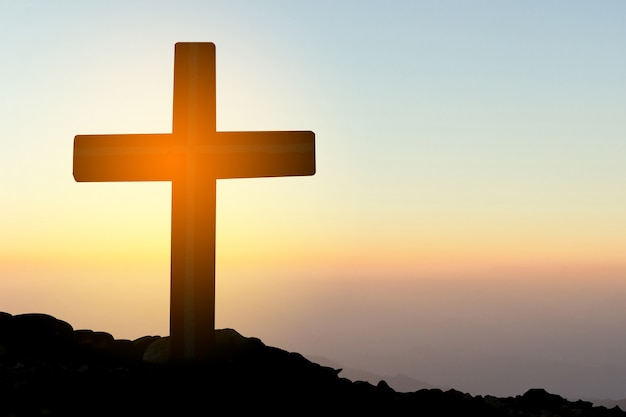 Concept conceptual yellow cross religion symbol silhouette in nature over sunset or sunrise sky Premium Photo