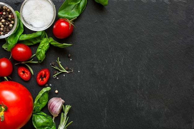 コンセプトクックは、暗い背景に野菜、スパイス、ハーブで動作します。 Premium写真
