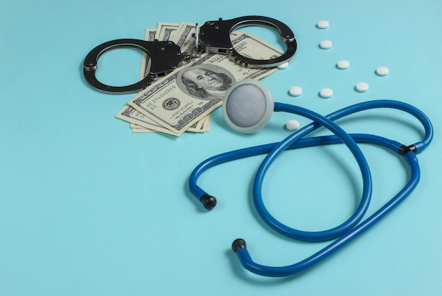 Concept of corruption in medicine. stethoscope, pills and handcuffs with hundred dollar bills on blue background. medical still life. punishment for crime Premium Photo