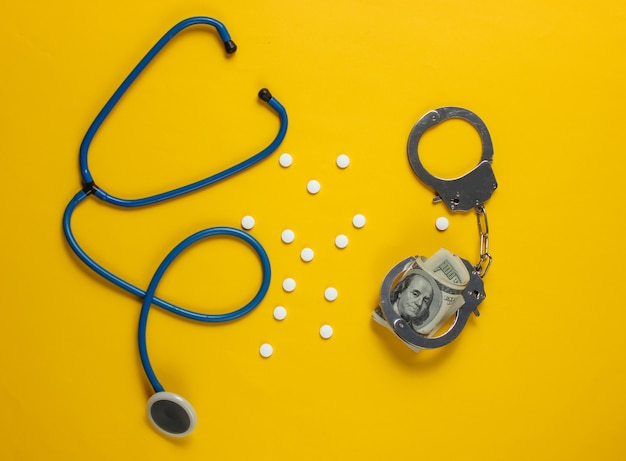 Concept of corruption in medicine. stethoscope, pills and handcuffs with hundred dollar bills on yellow background. medical still life. punishment for crime Premium Photo