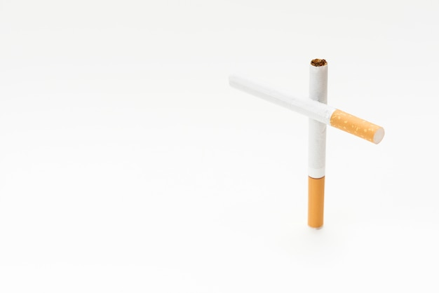 Concept of cross sign made from cigarette on white background Free Photo