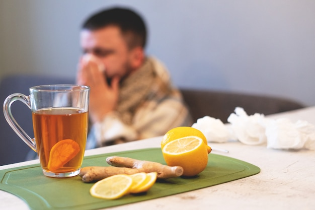 The concept of the disease, winter time. black tea, lemon and ginger on the table, Premium Photo