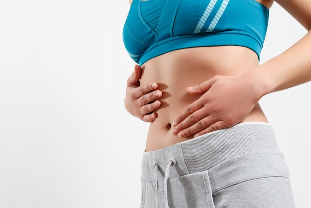 The concept of early pregnancy, proper nutrition, women's health. close-up photo of a slender beautiful belly and navel of a woman. she touches the two palms of her hands to her waist Premium Photo