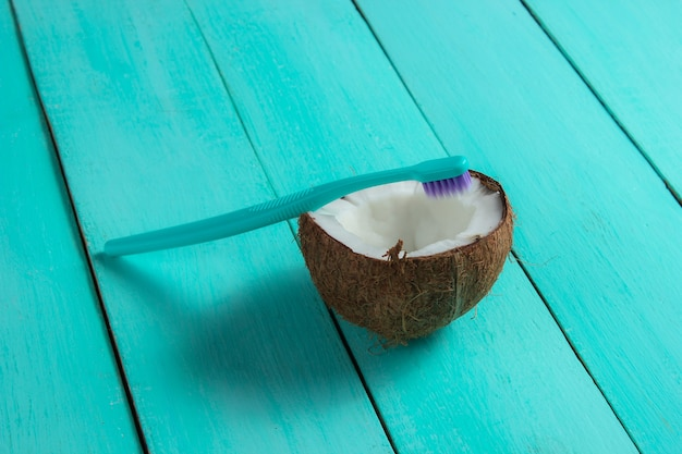 Concept of eco-friendly products for dental care. toothbrush and half coconut on a blue wooden background Premium Photo