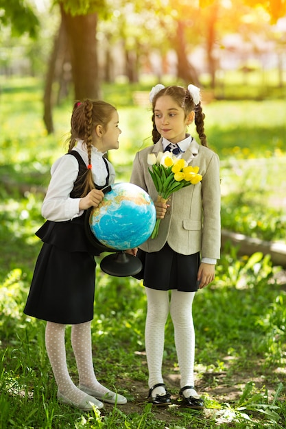 Concept - education. back to school. two cheerful caucasian girls schoolgirls with flowers and a globe, happy to be returning home after class in class Premium Photo
