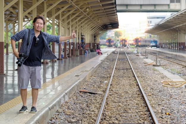 개념 자유형 여행 : 아시아 여행자 남성은 기차가 역에 도착하기를 기다리는 동안 철도 트랙에서 히치 하이킹 표지판으로 엄지를 사용합니다. 프리미엄 사진