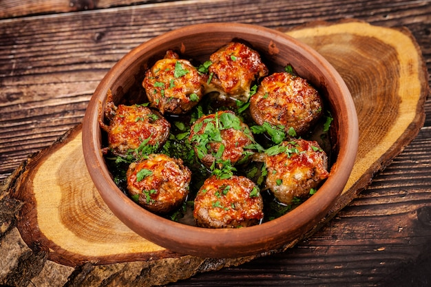 The concept of georgian cuisine. baked mushrooms champignons with meat and cilantro. serving dishes in a restaurant in a plate made of red clay. on a wooden background. copy space Premium Photo