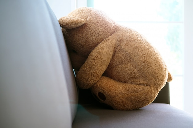 The concept of grief of children. the teddy bear sits on the couch inside the house, alone looking sad and disappointed. Premium Photo