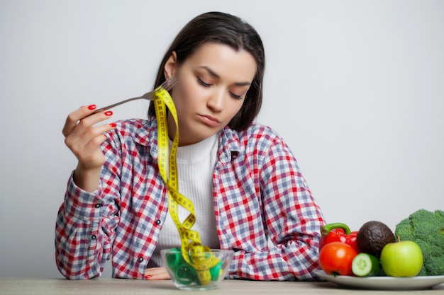 Concept of growing thin woman with plate full of tape measure Premium Photo