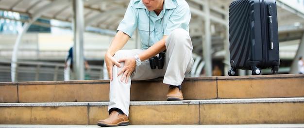 膝の痛みに苦しんでいる不幸な年配の男性。旅行と観光concept.health問題と人々のコンセプト。 Premium写真
