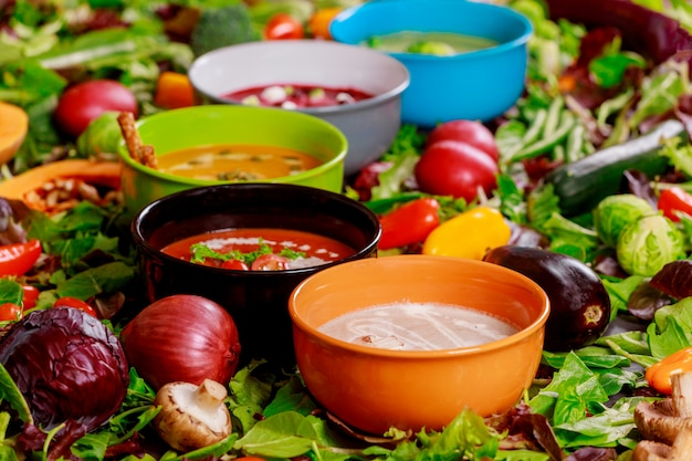 Concept of healthy eating or vegetarian food of colorful vegetables cream soups and ingredients for soup. Premium Photo