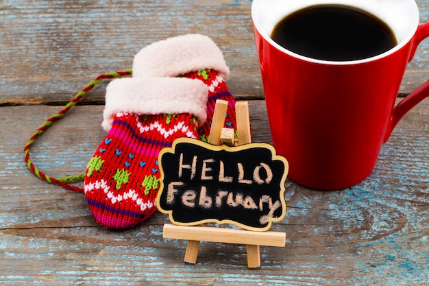 Concept hello february message on blackboard with a cup of coffee and mittens Premium Photo