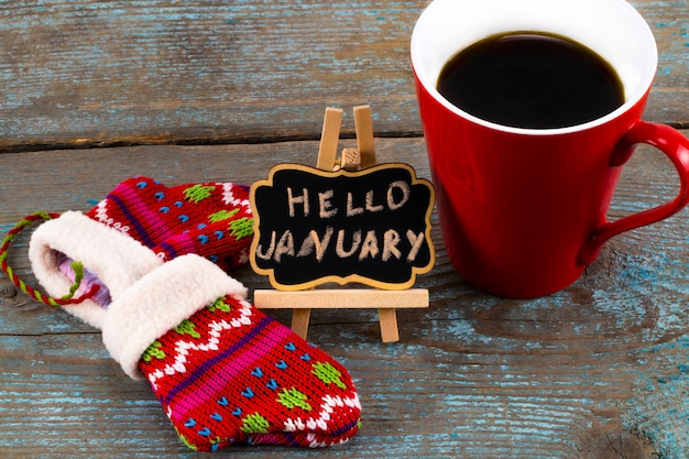 Concept hello january message on blackboard with a cup of coffee and mittens Premium Photo