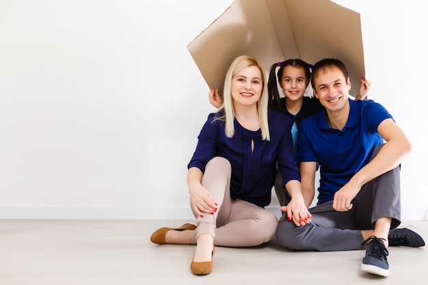 Концепция жилья молодой семьи. мать отец и ребенок в новом доме Premium Фотографии