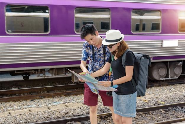 컨셉 라이프 스타일 여행 또는 여행 : 젊은 아시아 부부는 기차역에서 여행을 계획하기 위해지도를보고 있습니다. 프리미엄 사진