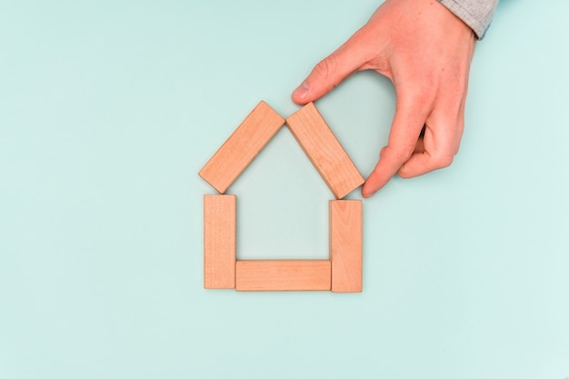 주택 구입 또는 임대의 개념. 손 집의 형태로 나무 블록을 보유 프리미엄 사진