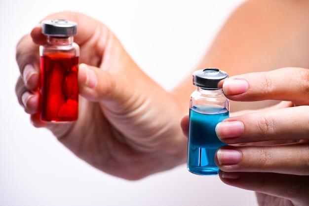 Концепция выбора лечения. крупным планом женщина руки, держа две ампулы. медицинские ампулы с жидкостью. красные и синие ампулы. Premium Фотографии