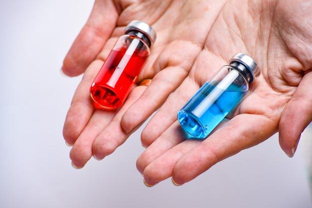 Концепция выбора лечения. крупным планом женщина руки, держа два флакона или ампулы. медицинские ампулы с жидкостью. красные и синие ампулы. Premium Фотографии