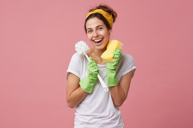 衛生、掃除、清潔、家事、家事のコンセプトです。家事をしながらトイレのブラシとスポンジを保持しているカジュアルな服装の若い白人主婦の肖像画 無料写真