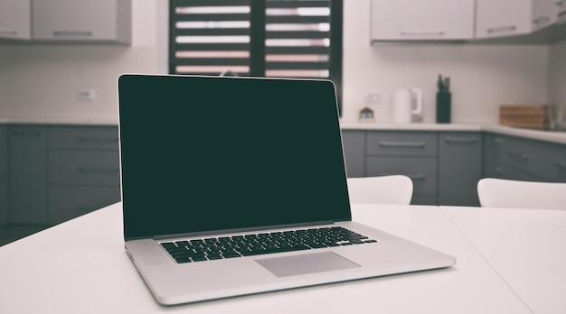 Концепция поиска рецептов с современным ноутбуком на столе на кухне Premium Фотографии