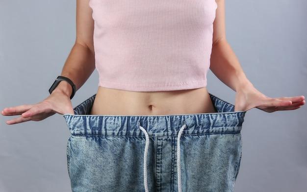 体重を減らすという概念。灰色のスタジオの背景に非常に大きなジーンズの女性。 Premium写真