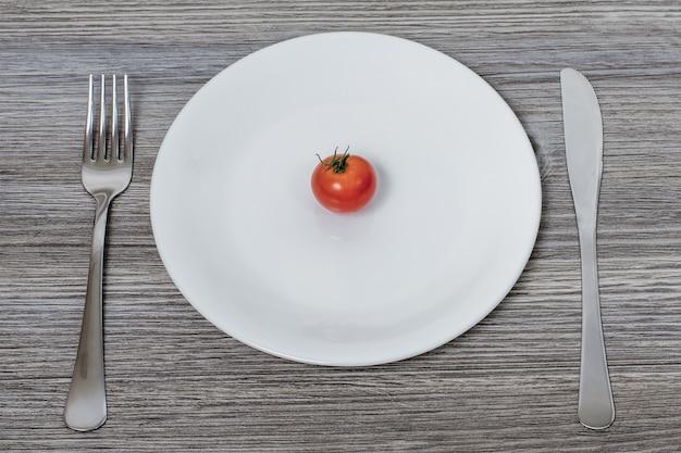 저칼로리 다이어트의 개념. 칼 붙이 흰색 접시에 작은 체리 토마토 프리미엄 사진