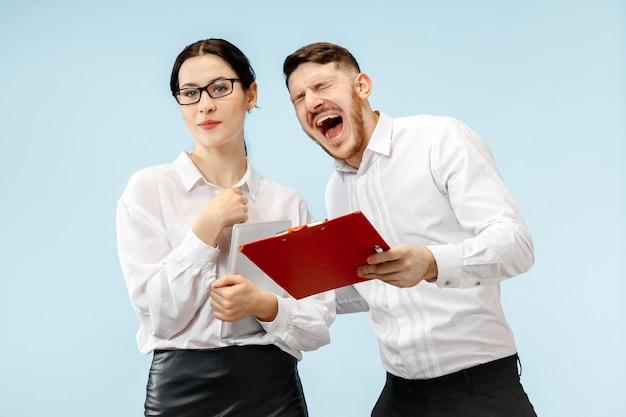 비즈니스 파트너십의 개념. 젊은 행복 웃는 남자와 여자는 파란색 벽에 서 무료 사진