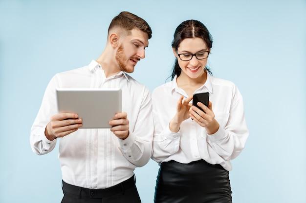 ビジネスにおけるパートナーシップの概念。スタジオで青い背景に対して携帯電話とタブレットで立っている若い幸せな笑顔の男と女 無料写真