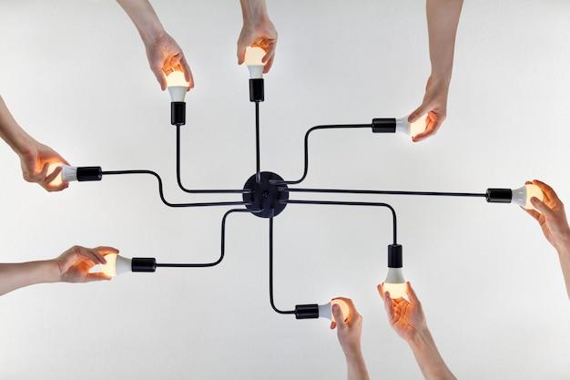 천장 조명에서 Led 램프를 교체 할 때 팀워크의 개념 또는 통합 된 행동의 예에 대한 공유 목적 프리미엄 사진