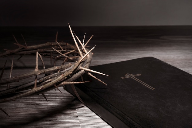 Концепция страстной недели. терновый венец в резком свете и библия лежат на столе. высокий контраст. Premium Фотографии
