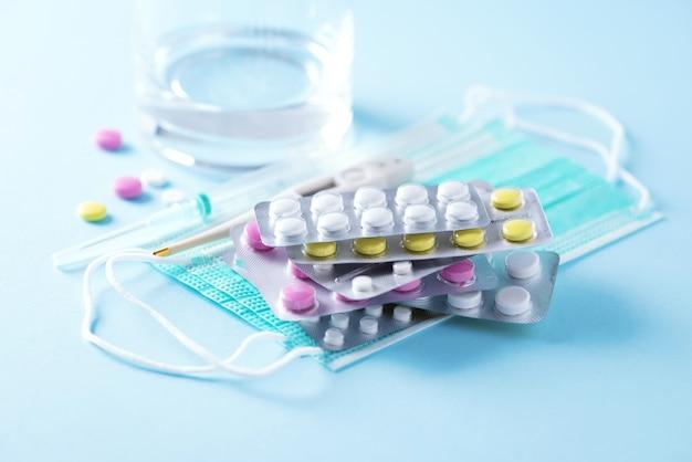 Концепция терапии, профилактика вирусного гриппа, вирусного приступа, таблетки от простуды, антибиотики и витамины, защитные медицинские маски для лица на синем фоне. коронавирус ковид-19. копировать пространство Premium Фотографии