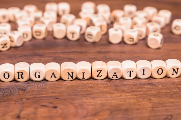 Concept of organization arranged with wooden cubes over wooden desk Free Photo