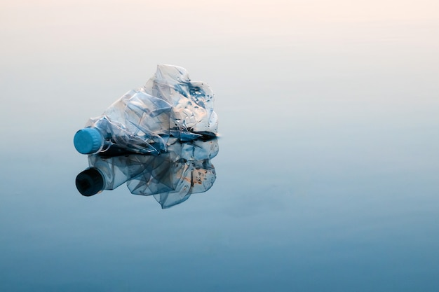Concept of pollution, creative. a plastic bottle floating in the ocean Premium Photo