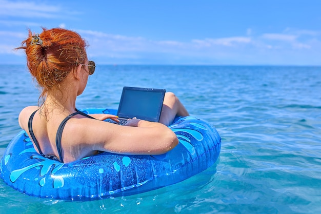 Concept of remote work. business woman sitting in a inflatable ring at sea Premium Photo