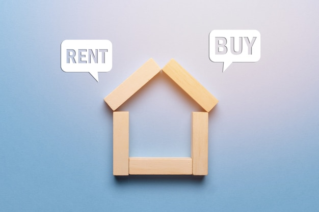 Concept of renting or buying real estate house made of wooden blocks with icons. Premium Photo