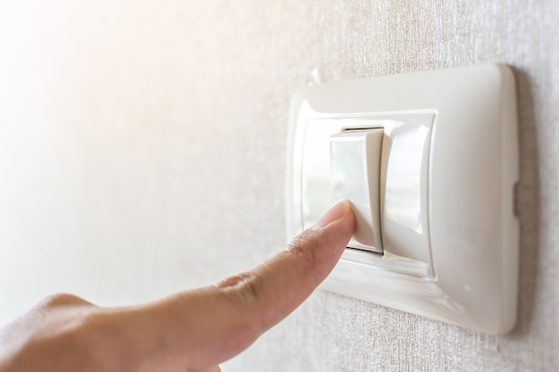 Concept save energy. hand turning off switch Premium Photo