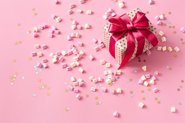 Il concetto di san valentino. confezione regalo con fiocco rosso sulla parete rosa. Foto Gratuite